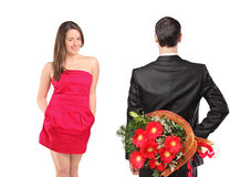 Man in black suit hiding flowers and woman. A man in black suit hiding  flowers and an attractive woman isolated on white background Stock Image