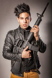 Man in black suit holding gun. Young middle eastern man with black leather jacket in black suit holding gun. studio shot Stock Images