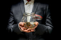 Man in black suit holding money jar with coins. On black background royalty free stock photos