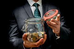 Man in black suit holding money jar with coins. Isolated on black background stock photo