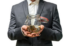 Man in black suit holding money jar with coins. Isolated on white background stock photography