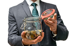 Man in black suit holding money jar with coins. Isolated on white background royalty free stock photos