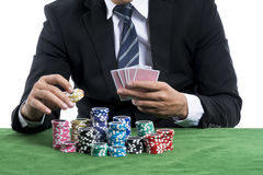 The man in black suit holding some chips for into the bets. Close up the Hands& x27;s man holding piles of chips to put into piles bets on green Stock Photos