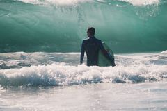 Man in Black Suit Holding Surfing Board Beside the Wave during Daytime Stock Image