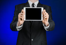 Man in a black suit holding a white tablet  Stock Images