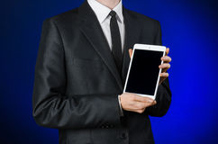 Man in a black suit holding a white tablet Royalty Free Stock Photo
