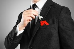 A man in a black suit holds the keys to the house. Key ring red. House royalty free stock photo