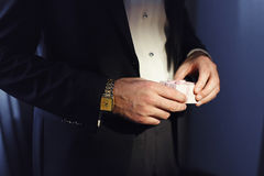 Man in the black suit holds little pink gift-box Royalty Free Stock Images