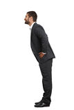 Man in black suit leaning forward Royalty Free Stock Photography
