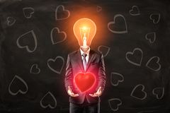 Man in black suit with light bulb instead head, levitating red glaring heart with his palms, standing against black stock illustration