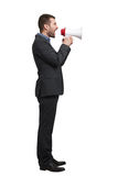 Man in black suit with megaphone. Young businessman in black suit screaming at megaphone. isolated on white background Stock Image