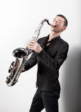 Man in black suit playing on saxophone against white background Royalty Free Stock Image
