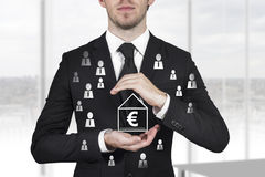 Man in black suit protecting euro house Stock Image