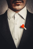 The man in the black suit with the red heart Royalty Free Stock Image