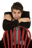 Man in black suit sit backwards on red chair arms folded Royalty Free Stock Photo