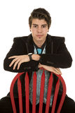 Man in black suit sit backwards on red chair serious Royalty Free Stock Image