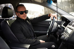 Man in  black suit sitting behind the wheel Stock Photography