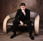 Man in black suit sitting on a sofa Stock Images