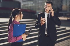 A man in a black suit is telling something on the phone while a journalist looks at him. TV reporter at work. Businessman is holding a business conversation on Royalty Free Stock Image
