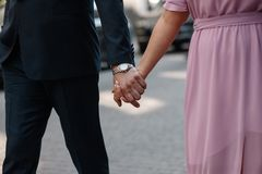 A man in the black suit and a woman in the pink dress are holding hands closeup. They are walking at the street.  stock photos