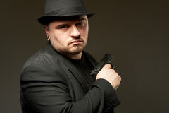 Man in black suite with gun. Royalty Free Stock Images