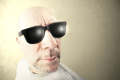 Man with black sunglasses looking forward. Beige background Royalty Free Stock Image