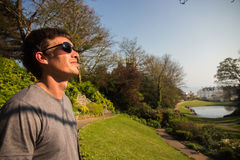 Man in black sunglasses looking at the sun in amazing park. Looking in the future Stock Image