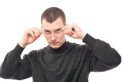 Man in a black sweater, correcting his glasses. On a white background Stock Image