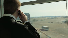 Man in black sweater stands near window and talks on cell phone. He is situated in building of airport and waits until start of registration on board of stock video