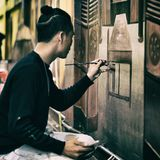 Man In Black Sweatshirt Holding Black Paint Brush Painting the Wall Royalty Free Stock Photo