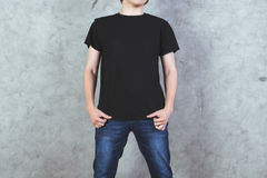 Man in black t-shirt. Front view of young man in empty black shirt and jeans on concrete wall background. Mock up stock photos