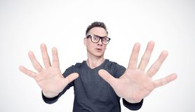 Man in a black T-shirt and glasses is afraid, making stop with his hands. Deep fear concept emotion stock photo