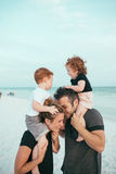 Man in Black T Shirt With His Family Standing in White Sand Near Body of Water Under White Sky during Daytime Royalty Free Stock Images