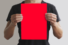 Man in black t shirt holding blank red A4 paper vertically. Leaf. Let presentation. Pamphlet hold hands. Man show clear offset paper. Sheet template. Isolated on Royalty Free Stock Photo
