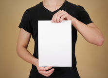 Man in black t shirt holding blank white A4 paper. Leaflet presentation. Pamphlet hold hands. Man show clear offset paper. Sheet. Template stock photos