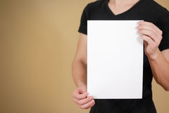 Man in black t shirt holding blank white A4 paper. Leaflet prese Stock Images
