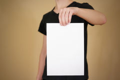 Man in black t shirt holding blank white A4 paper. Leaflet prese Royalty Free Stock Images