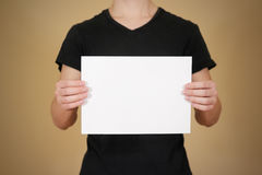 Man in black t shirt holding blank white A4 paper. Leaflet presentation. Pamphlet hold hands. Man show clear offset paper. Sheet. Template royalty free stock images