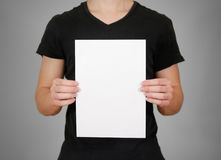 Man in black t shirt holding blank white A4 paper. Leaflet presentation. Pamphlet hold hands. Man show clear offset paper. Sheet. Template. Isolated on grey royalty free stock image