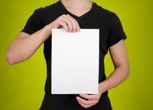 Man in black t shirt holding blank white A4 paper. Leaflet presentation. Pamphlet hold hands. Man show clear offset paper. Sheet. Template stock photo