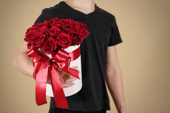 Man in black t shirt holding in hand rich gift bouquet of 21 red. Roses. Composition of flowers in a white hatbox. Tied with wide red ribbon and bow royalty free stock photos