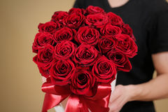 Man in black t shirt holding in hand rich gift bouquet of 21 red Stock Photo