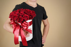 Man in black t shirt holding in hand rich gift bouquet of 21 red. Roses. Composition of flowers in a white hatbox. Tied with wide red ribbon and bow royalty free stock image