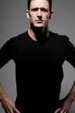 Man in black t-shirt posing on gray background. Royalty Free Stock Images