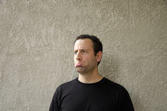 Man in a black t-shirt with a sad expression. Royalty Free Stock Images