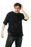 Man in a black T-shirt scratches his head. Royalty Free Stock Image