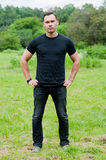 Man in a black t-shirt stands on the grass Stock Images