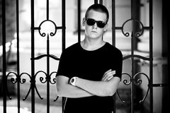 Man in black t-shirt and sunglasses leaning to metal fence Royalty Free Stock Photo
