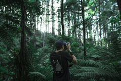 Man in Black T Shirt Taking Photos in Forest Stock Image