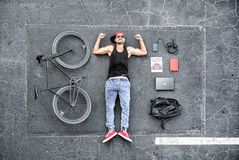 Man in Black Tank Top Laying on Gray Concrete Surface Near Black Bike royalty free stock image